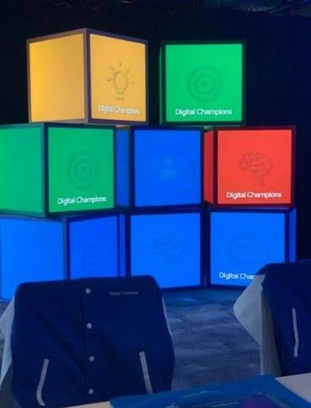 colourful, illuminated blocks stacked behind a chair with a Digital Champions logo